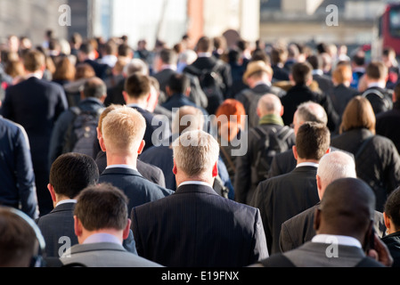Commuters crossing crowded London Bridge on the way home from work, UK - Stock Photo