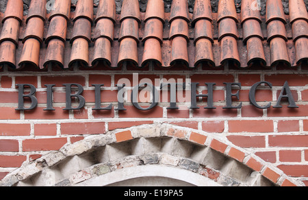 Library sign written in latin on red brick wall - Stock Photo