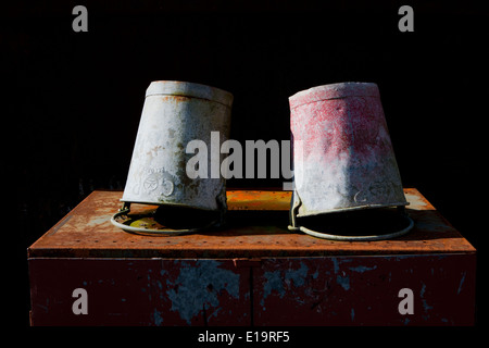 Two galvanized buckets with faded paint resting upside down on rusty metal. - Stock Photo