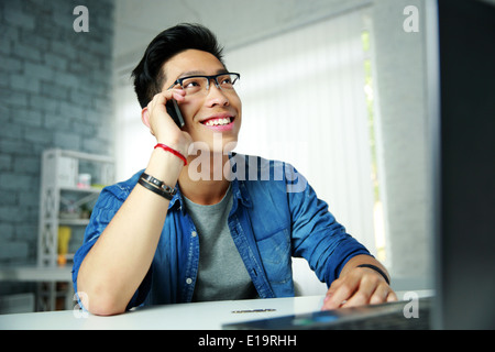 Young happy asian man talking on the phone at his workplace in office - Stock Photo