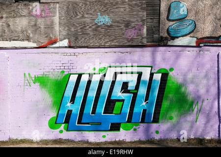 Graffiti (Street art) tag on the side of a brick and wooden structure.