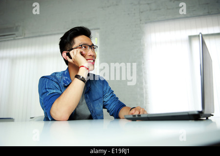 Happy asian man sitting at his workplace in office and talking on the phone - Stock Photo