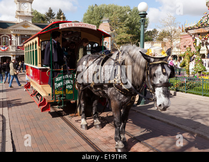 A horse-drawn tram in the central Plaza of  Disney Land Paris. - Stock Photo