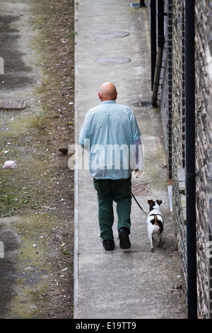 Aberystwyth, Wales, UK. A bald-headed man and his Jack Russell dog walk down an alleyway. Viewed from above and - Stock Photo