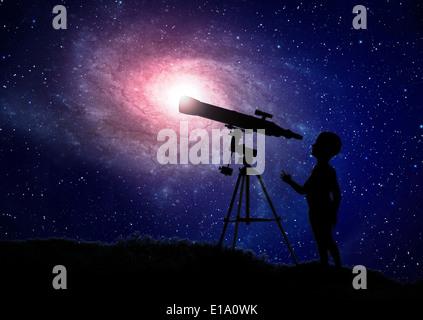 Small boy looking through a telescope - Stock Photo