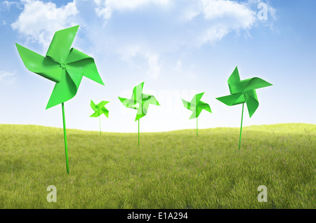 Pinwheel windmills in a field of grass - renewable energy concept - Stock Photo