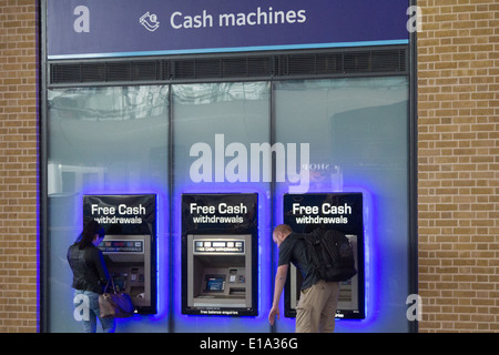 Woman and man withdrawing cash from an ATM machine at Kings Cross railway station - Stock Photo