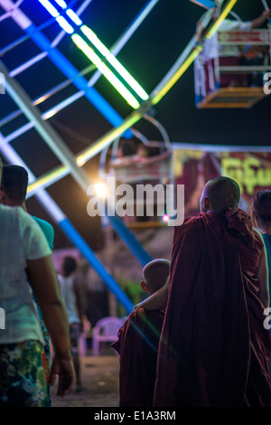 Two young monks look towards a ferris wheel at the water festival fair near their temple in Bago, Myanmar. - Stock Photo