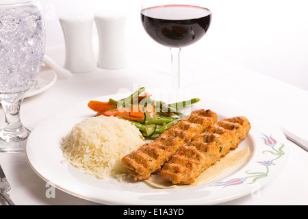 Chicken Adana kebap served with rice pilaf and green vegetables and some carrots, complimented with red Vine and - Stock Photo