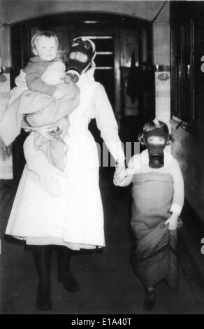 BRITISH HOME FRONT WW2 A nurse leads a child and babe in arms to the shelter during a mock gas attack. - Stock Photo