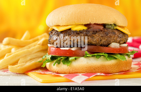 A classic style cheeseburger with beef, cheese, lettuce, tomatoe, onion, mustard, ketchup, and relish with french - Stock Photo