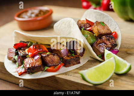 Two beef fajitas with red onion, peppers, cilantro, and lime. - Stock Photo
