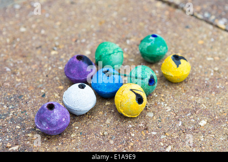 Colorful round smoke bombs naturally on the paver street some of them used some of them not. They have purple, green, - Stock Photo