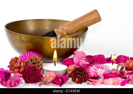 Studio shot of a tibetan bowl, some pink flowers and candles, over white background. - Stock Photo