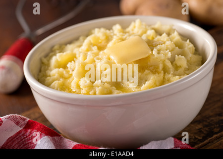 A bowl of creamy delicious mashed potatoes with melted butter. - Stock Photo