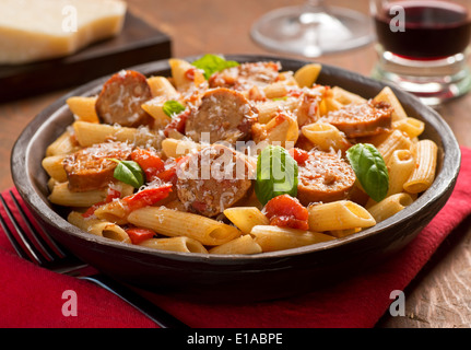 Cajun style pasta with penne, spicy sausage, red peppers, and tomato sauce with freshly grated parmesan cheese. - Stock Photo