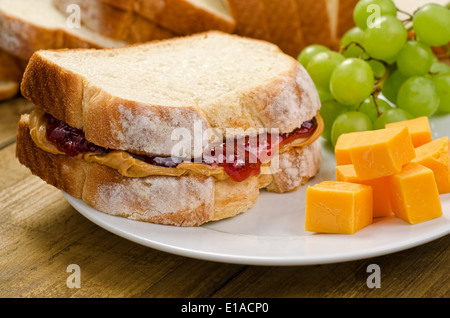 A nutritious peanut butter and jelly sandwich with cheddar cheese and grapes. - Stock Photo