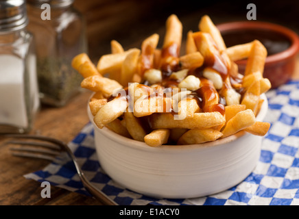 Classic French Canadian poutine with french fries, gravy, and cheese curds on a rustic tabletop. - Stock Photo
