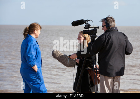 TV news presenter interviews RSPCA seal rescue worker at Winterton following release of a group of rehabilitated - Stock Photo