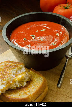 A hearty bowl of home made tomato soup and a grilled cheese sandwich. - Stock Photo