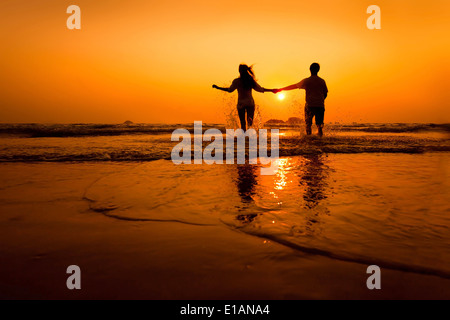 silhouettes of couple running to the sea on the beach at sunset - Stock Photo