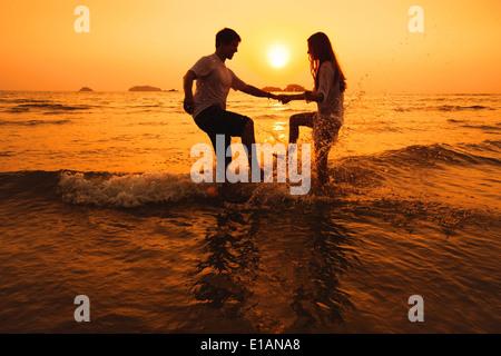 couple having fun in the sea at sunset beach - Stock Photo