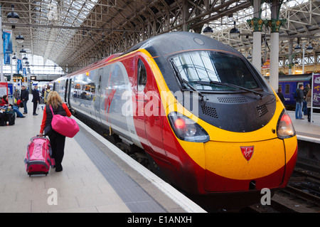 Lady passenger walking on platform with luggage to the Virgin Pendolino train at Manchester Piccadilly Station; - Stock Photo