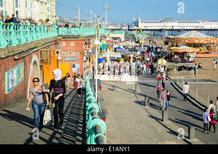 English seaside resort town on a warm summer day, with crowds of people on the promenade. Brighton sea front; summer; - Stock Photo