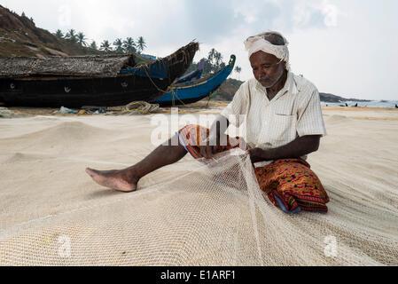Fisherman repairing fishing nets on the beach, Vizhinjam, Kerala, India - Stock Photo