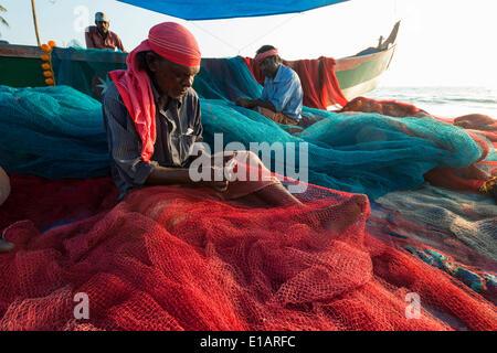 Fishermen repairing fishing nets on the beach, Varkala, Kerala, India - Stock Photo