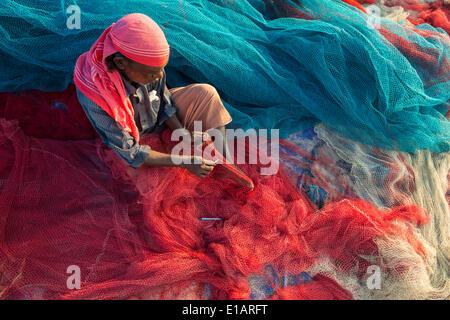 Fisherman repairing fishing nets, Varkala, Kerala, India - Stock Photo