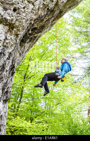 Female climber, woman climbing rock, abseiling from the top. - Stock Photo