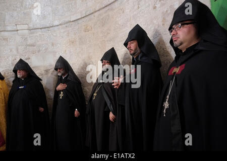 Armenian priests in their black hooded copes taking part in a ceremony at Aedicula of the Ascension chapel on the - Stock Photo