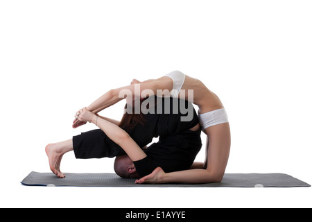 Side view of healthy couple doing yoga in studio - Stock Photo