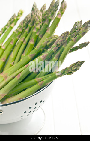 green asparagus in colander on white background - Stock Photo