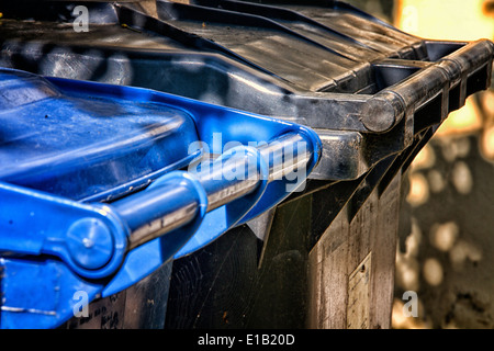 A blue and a black wheelie bin holding household waste or trash, Suffolk, England - Stock Photo