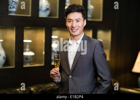 Young businessman with champagne - Stock Photo