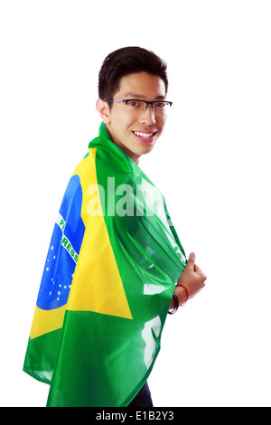 Side view portrait of a man holding Brazilian flag over white background - Stock Photo