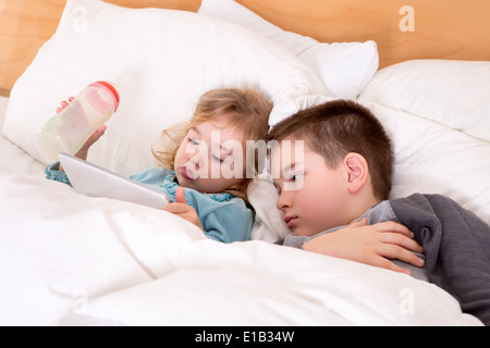 Cute little boy and girl reading a bedtime story on a tablet-pc before sleeping, lying in a big comfortable bed - Stock Photo