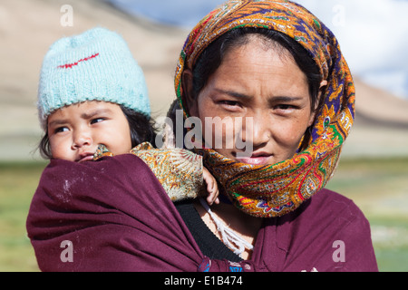 Woman in colorful patterned headscarf carrying child in a baby sling, region of Tso Kar, Rupshu, Changtang, Ladakh, - Stock Photo