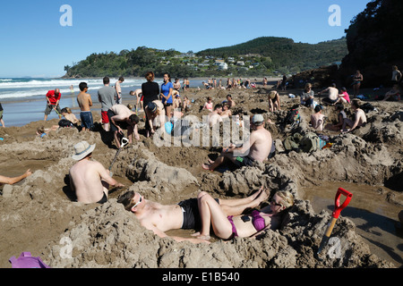 Tourists relaxing in hot pools dug on beach - Stock Photo
