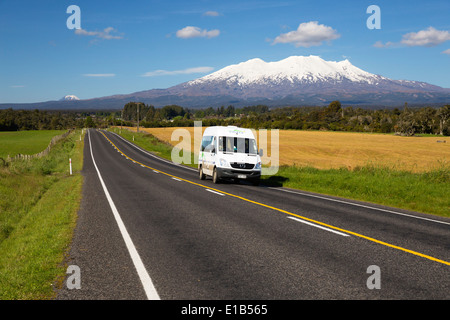 Motorhome driving along road below Mount Ruapehu and Mount Ngauruhoe - Stock Photo
