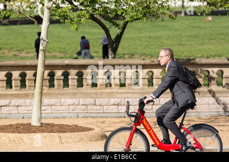 Businessman on Capital Bikeshare bicycle rides past the Capitol in Washington DC - Stock Photo