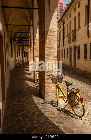 Bicycles standing at the side of a cobbled road leading the eye along a traditional Italian arched walkway in Treviso, - Stock Photo