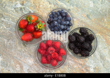 Overhead view of a selection of different fresh berries in glass jars including succulent ripe strawberries, blackberries, - Stock Photo