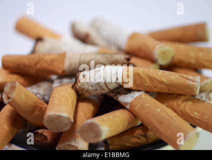 Ashtray filled with used cigarette butts on white background - Stock Photo