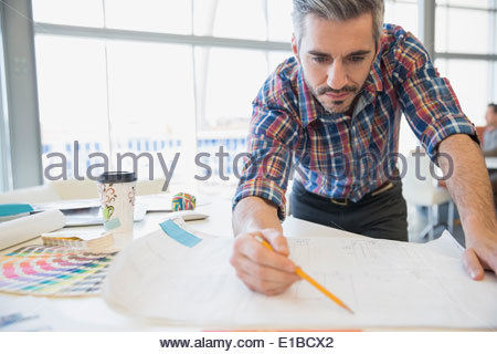 Creative businessman looking at blueprint in office - Stock Photo