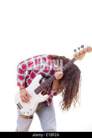man in red shirt with tousled hair playing electric bass guitar - Stock Photo