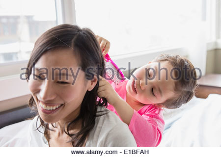 Daughter brushing mothers hair - Stock Photo