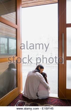 Mother and daughter hugging in doorway - Stock Photo